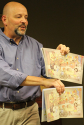 Michael Hale showing examples of illustrations. Photo by Bing Brown.
