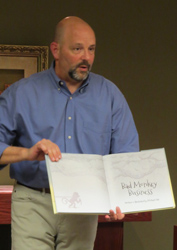 """Michael Hale showing """"Bad Monkey Business,"""" which he wrote and illustrated. Photo by Carol Osman Brown."""